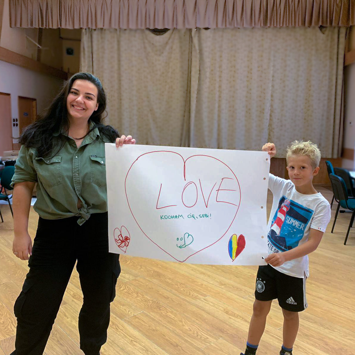 Alexandra and her student holding up a drawing he made for her with a big heart